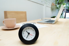 Wood table with black clock, coffee cup, laptop and resume infor Stock Photo