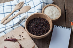 Wood table with black and white rice grain on wood plate. Royalty Free Stock Photography