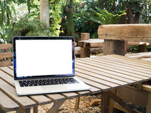 Wood table with blank screen on laptop at parkland. Wood table with blank screen on laptop at natural parkland Royalty Free Stock Image
