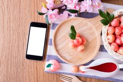Wood table with blank screen on smart phone and Delectable imitation fruits, Fruit Shaped Mung Bean. S, Thai traditional dessert royalty free stock images