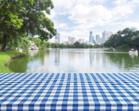 Wood table with blue table cloth on blur park background for display montage your products Stock Photography