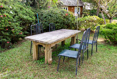 Wood table with chairs in shady garden Royalty Free Stock Image