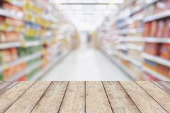 Wood table with Empty Supermarket aisle shelves. Abstract blur defocused business background, product display template stock photo