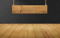 Wood table with hanging wooden sign on black concrete wall Stock Image