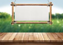 Wood table with hanging wooden sign on green nature blurred background. For display Royalty Free Stock Image