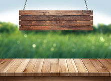 Wood table with hanging wooden sign on green nature blurred background stock image