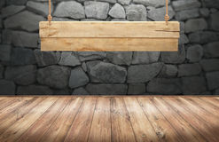 Wood table with hanging wooden sign on stone wall Stock Photo