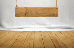Wood table with hanging wooden sign on white fabric background Royalty Free Stock Photography
