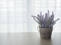 Wood table with left free space and purple lavender flowerpot on. Beautiful white drape window texture background at living room stock photography