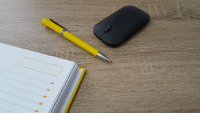 Wood table with mouse, pen and agenda royalty free stock photography