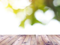 Wood table over blurry abstract green background. With white bokeh heart shape for natural springtime. Love environment concept. Montage style Royalty Free Stock Images