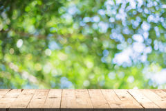 Wood table perspective and green leaf bokeh blurred Royalty Free Stock Photos