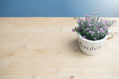 Wood table with pink rose flower on flower pot and concrete wall. View from above flower pot stock photography