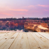 Wood table and pond water with blurred sunset Stock Photography