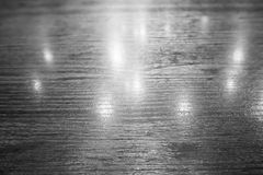 Wood table and reflection of light bulb. 