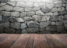 Wood table with stone wall background Royalty Free Stock Images