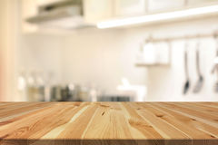 Wood table top (as kitchen island) on blur kitchen interior back stock images