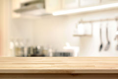 Wood table top (as kitchen island) on blur kitchen interior back. Ground - can be used for display or montage your products Stock Photos