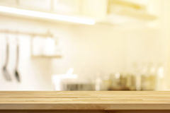 Wood table top as kitchen island on blur kitchen interior back stock images