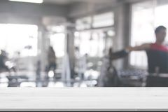 Wood Table Top Background on blurred fitness gym abstract background of exercise equipments for backdrop composition for. Website magazine or graphic design royalty free stock photo