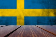Wood Table Top and Grunge Sweden Flag on concrete wall. stock photo