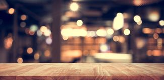 Wood table top Bar with blur light bokeh in dark night cafe Royalty Free Stock Images
