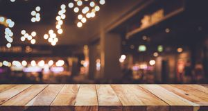 Wood table top Bar with blur light bokeh in dark night cafe Royalty Free Stock Photos