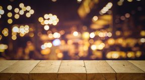 Wood table top Bar with blur light bokeh in dark night cafe Stock Images