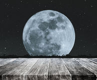 Wood table top with beautiful full moon at night with stars and silhouette glass lawn. full moon background Royalty Free Stock Images