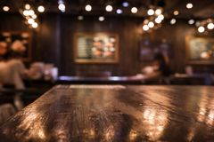 Wood table top on blur cafe restaurant in dark night Royalty Free Stock Images