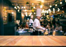 Wood table top with blur chef cooking in bar restaurant stock photo
