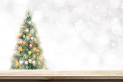 Wood table top on blur Christmas tree background in snowfall royalty free stock images