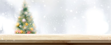 Wood table top on blur Christmas tree banner background. Wood table top on blur Christmas tree background in snowfall, panoramic banner Stock Photos