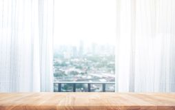 Wood table top on on blur of curtain with window city view Stock Photos