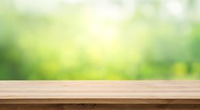 Wood table top and blur of fresh green bokeh from garden background. For product display and natural concept stock photography