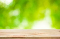 Wood table top and blur of fresh green bokeh from garden. Background .For product display and natural concept royalty free stock image