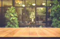 Wood table top on blur glass wall cafe background. Royalty Free Stock Image