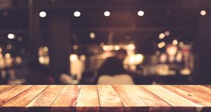 Wood table top with blur light bokeh in dark night cafe Royalty Free Stock Image