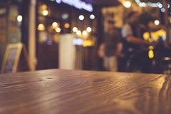 Wood table top with blur of lighting in night cafe restaurant community. Background/selective focus Stock Photo