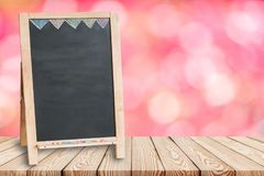 Wood table top on blur pink background of flower with blank blackboard. Can be used for display or montage your products royalty free stock image