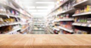 Wood table top on blur of supermarket product shelf background.