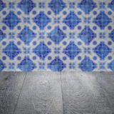Wood table top and blur vintage ceramic tile pattern wall Stock Photography