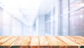 Wood table top on blur white glass wall background form office. Building.For montage product display and design key visual layout stock photos
