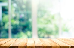 Wood table top on blur of window with garden flower background