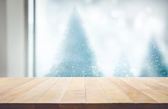 Wood table top on blur window view with pine tree in snow fall o