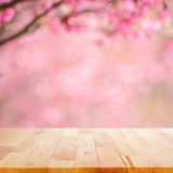 Wood table top on blurred background of pink cherry blossom flowers. Wood table top on blurred background of pink cherry blossom flower - can used for display or Royalty Free Stock Images