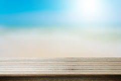 Wood table top on blurred beach background, summer concept. Royalty Free Stock Images