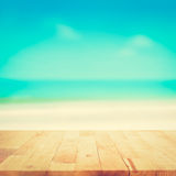 Wood table top on blurred beach background, vintage tone Stock Image