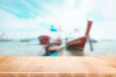 Wood table top on blurred blue sea and boat on beach background royalty free stock images