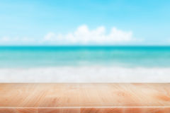 Wood table top on blurred blue sea and white sand beach backgrou. Nd - can be used for display or montage your products Stock Image